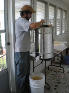 Stephen turning the extractor and honey draining into the bucket